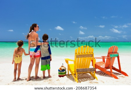 Family of mother and kids enjoying vacation at tropical beach with two colorful adirondack wooden chairs on white sand and turquoise ocean water in Caribbean - stock photo