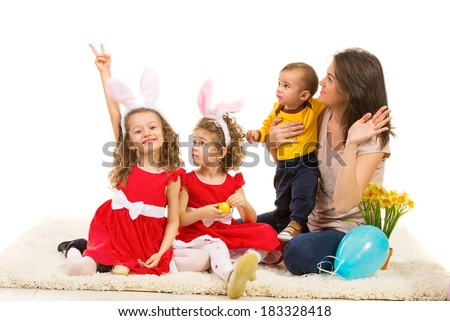 Family of mother and kids looking away in left part of image while one of girls showing victory sign hand gesture - stock photo
