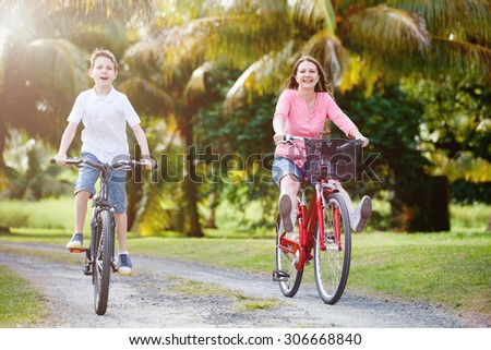 Family of mother and son biking at tropical settings having fun together - stock photo