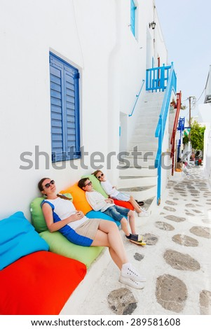 Family of mother and two kids relaxing on a colorful pillows at outdoor cafe on street of traditional greek village - stock photo