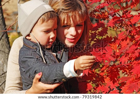 family of mother with kid teaching botany in the fall forest