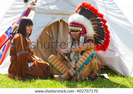 family of North American Indians sits at a wigwam - stock photo