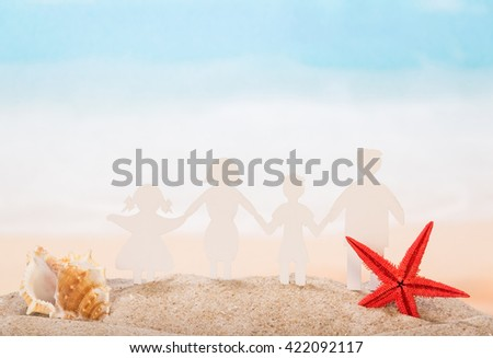 Family of paper, seashell and star in the sand against the sea.