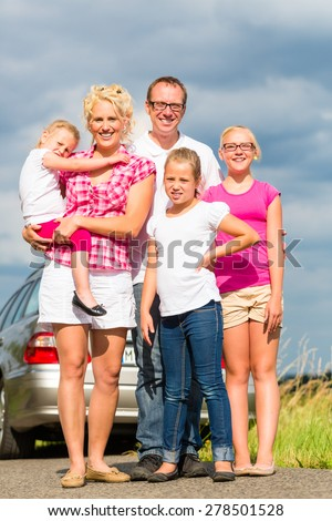 Family of Parents and children standing in front of car in countryside - stock photo