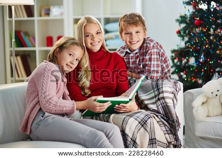 Family of siblings and their mother having rest at home on Christmas evening - stock photo