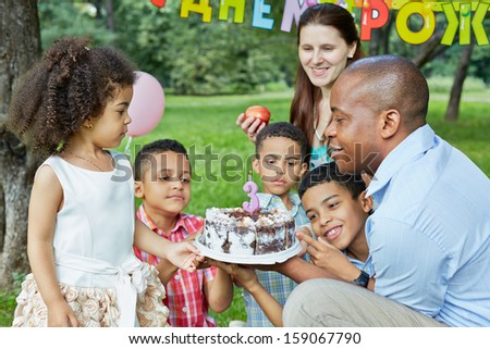 Family of six looks at birthday cake with burning candle on it, happy birthday sign behind theirs backs