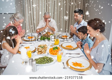 Family of six saying grace before meal at dining table against snow falling