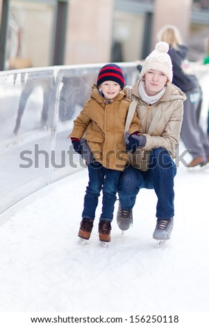 family of smiling young mother and her little son at skating rink - stock photo