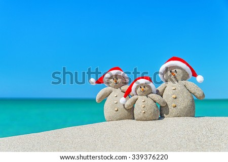 Family of Snowmen in santa hats at tropical beach. New Year's and Christmas holiday in hot countries concept. - stock photo