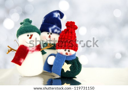 Family of snowmen with twinkling silver light background - stock photo