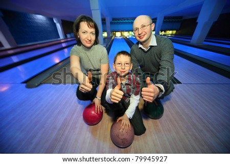 Family of squatting in bowling club and shows  hands of ok, focus on  boy - stock photo