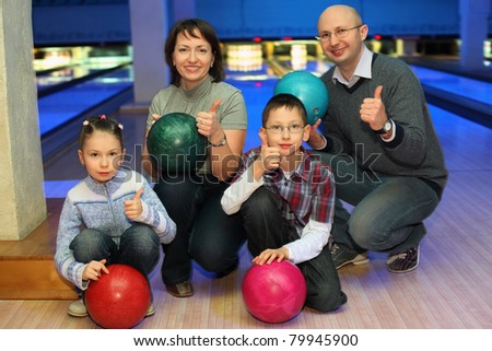 Family of squatting in bowling club and shows  hands of ok, focus on children - stock photo
