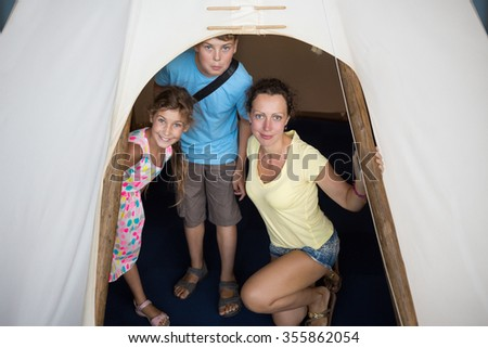 Family of three are standing into tepee in National Museum of the American Indian. - stock photo