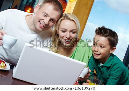 Family of three being amazed with the stuff displayed on the laptop screen - stock photo