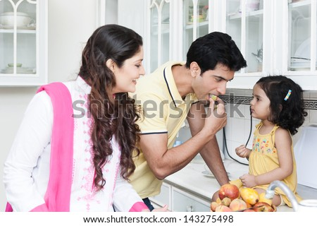 family of three eating fruits in the kitchen, Indian family in the kitchen,