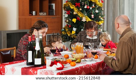 family of three generations  celebrating Christmas  over holiday table at home interior