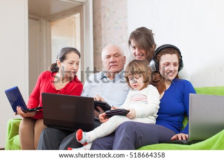 family of three generations uses few various devices in home