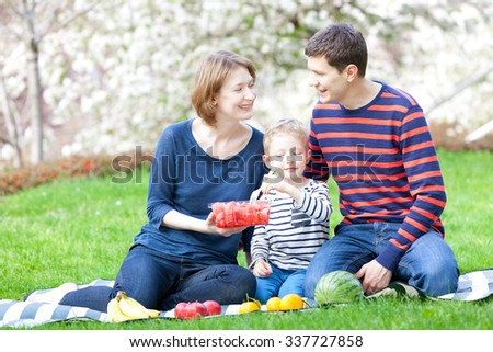 family of three having a picnic in the park at spring time - stock photo