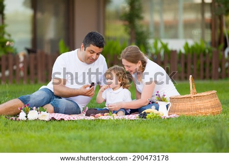 Family of three having picnic.