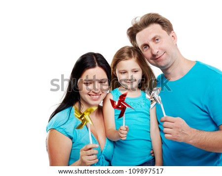Family of three in blue shirts with windmills in their hands.