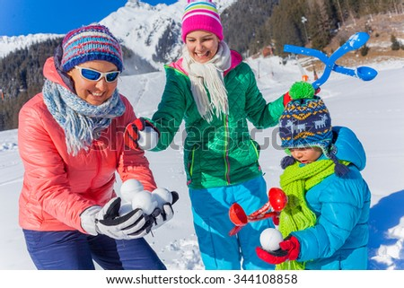 Family of three - little boy with his sister and mother having fun in the snow