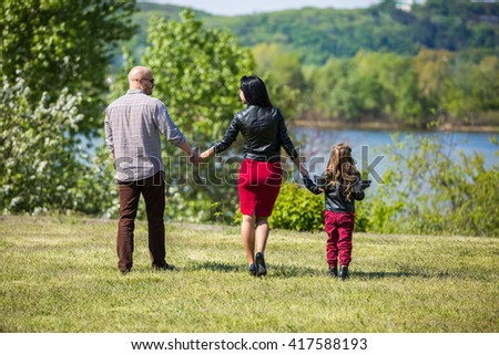 Family of three members walking in the park near river