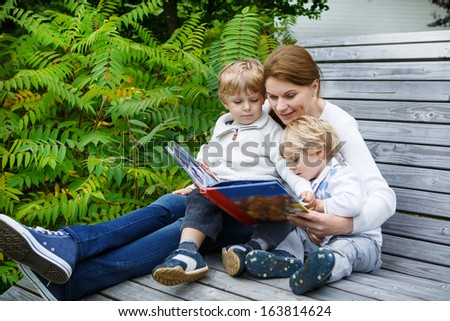 Family of three (mother and two sibling boys) sitting on bench in park and reading fairytale book together. - stock photo
