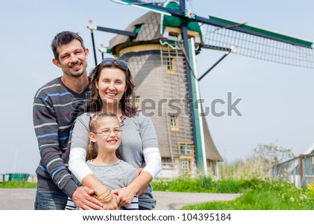 Family of three near windmill in Holland - stock photo