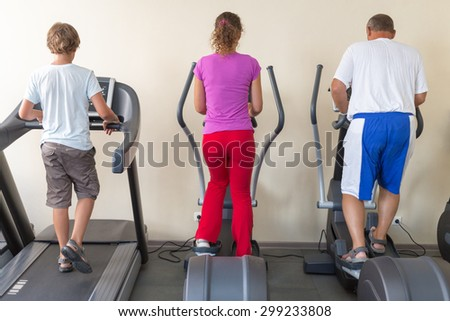 family of three on treadmills in a gym - stock photo