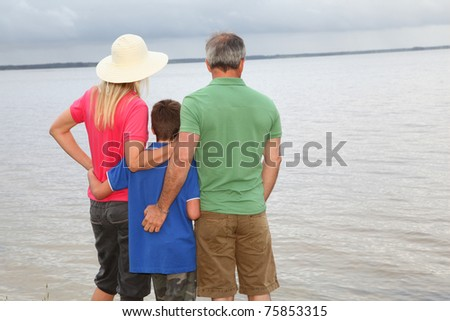 Family of three people on lake side - stock photo