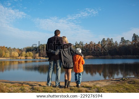 Family of three people on lake side. father mother and son  - stock photo