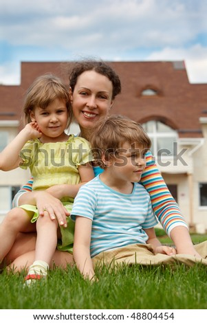 Family of three people on lawn in front of house. Mother hugging her daughter and son. - stock photo