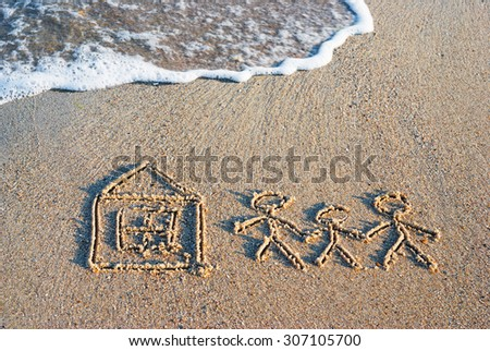 Family of three people with little house drawn in the sand of sea beach - stock photo
