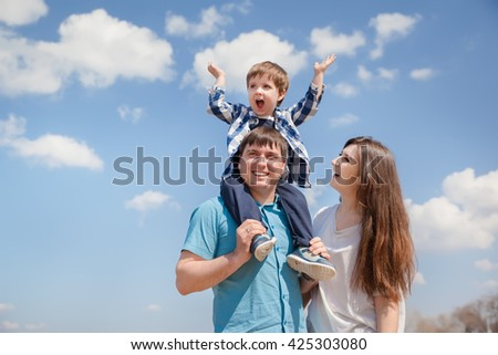 Family of three people, young parents and a little son on a sky background - stock photo