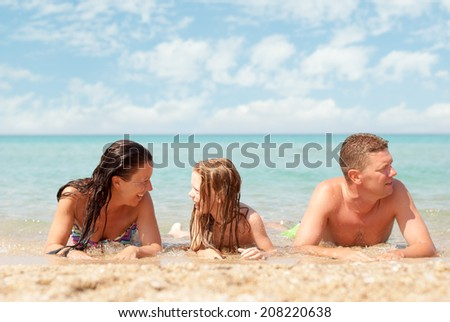 Family of three relaxing at beach