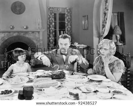 Family of three sitting together having dinner - stock photo