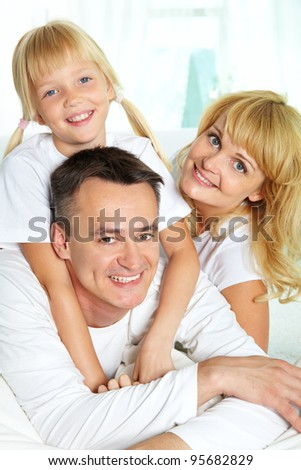 Family of three spending time together and smiling at camera - stock photo