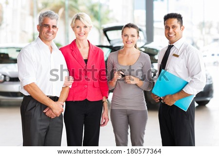 family of three standing with salesman at vehicle dealership after buying a new car - stock photo