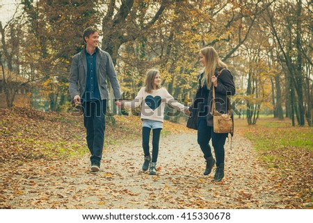 Family of three walk in a park on an autumn day. - stock photo