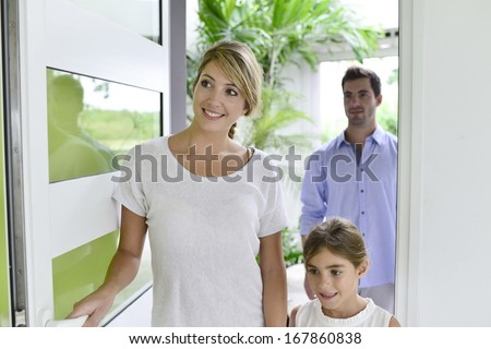 Family of three walking in new home - stock photo