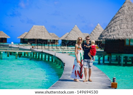 Family of three walking on the bridge towards to water bungalows on Maldives - stock photo