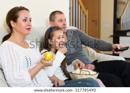 Family of three watching movie in domestic interior. Focus on woman - stock photo