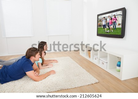 Family of three watching TV while lying on rug at home
