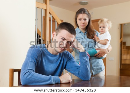 Family of three with baby having quarrel at home - stock photo