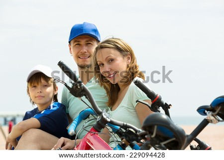 Family of three with cycles behind at seaside in summer day  - stock photo