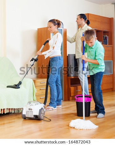 family of three with teenage boy cleaning with vacuum cleaner in living room