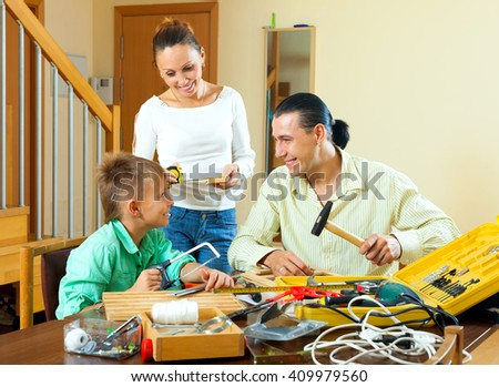 Family of three with teenage boy making something with the working tools at home - stock photo