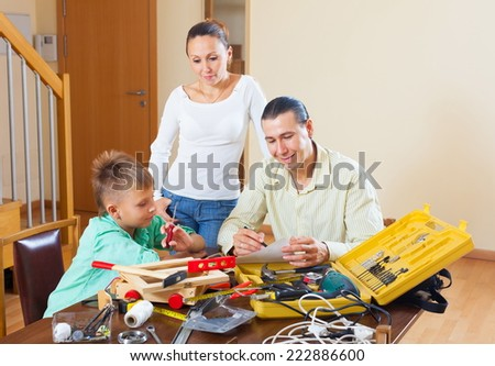 Family of three with teenager modeling something with the working tools - stock photo
