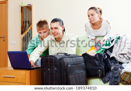 Family of three with teenager reserving tickets and choosing clothes for vacation in the living room - stock photo