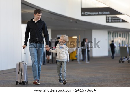 family of two at the airport with luggage - stock photo